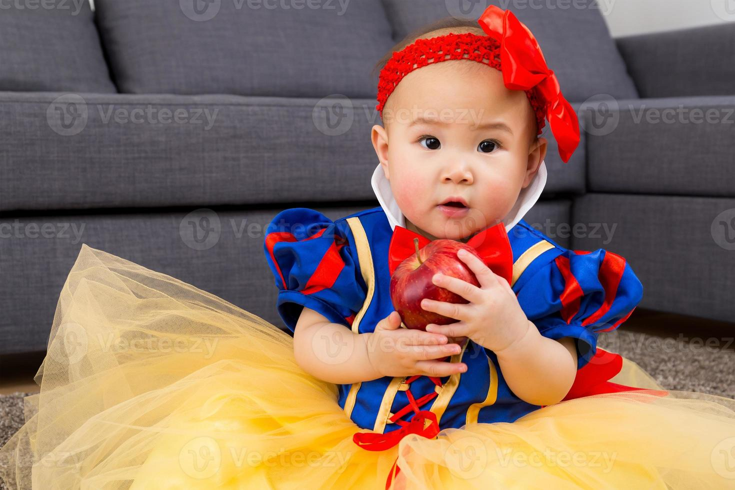Baby girl holding an apple with party dressing photo