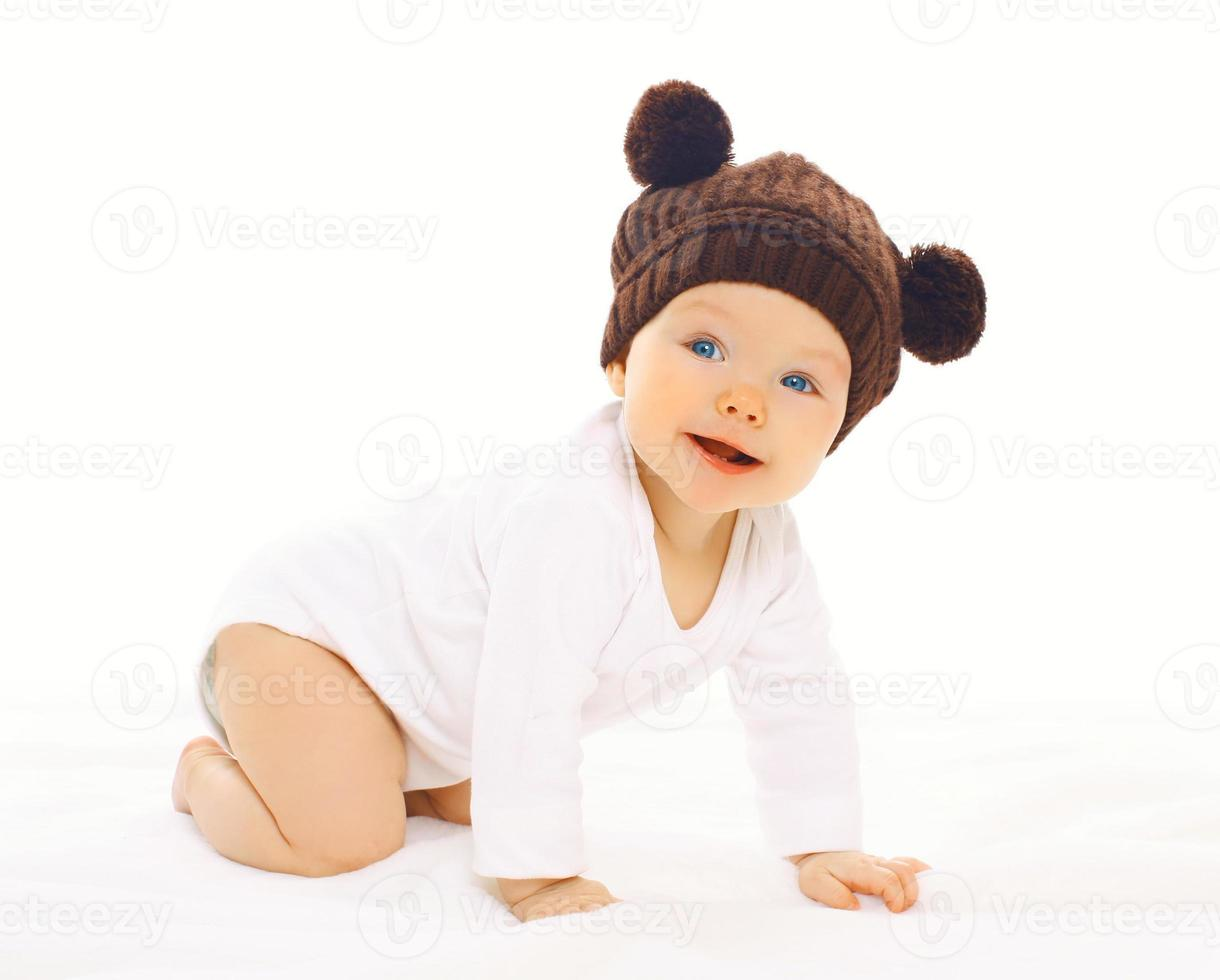 Portrait positive baby in knitted brown hat crawls photo