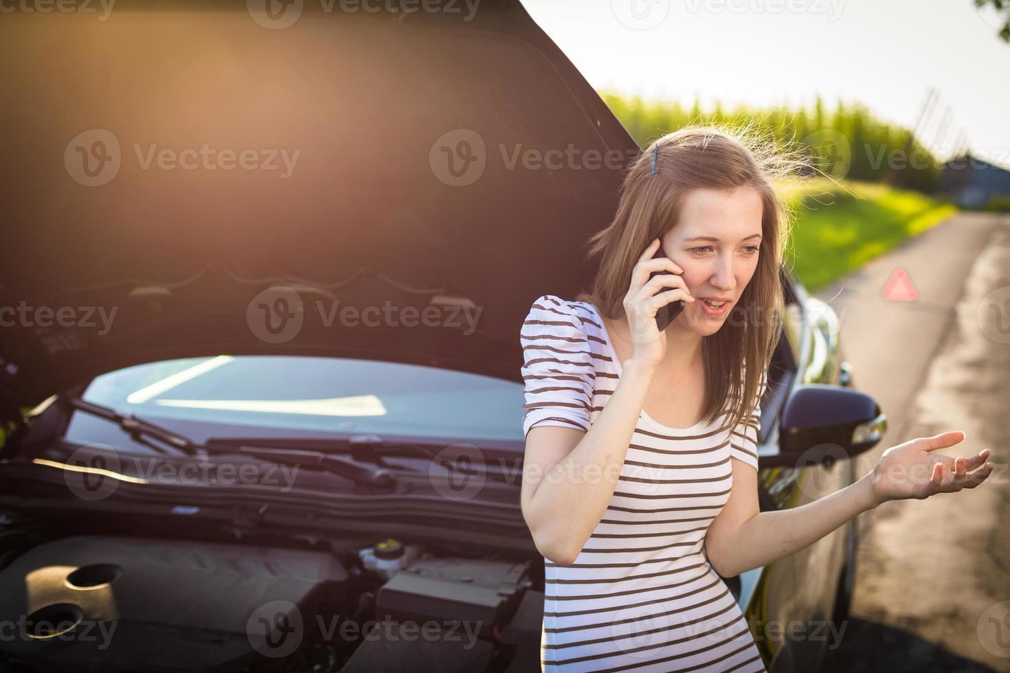 Pretty, young woman calling the roadside service photo