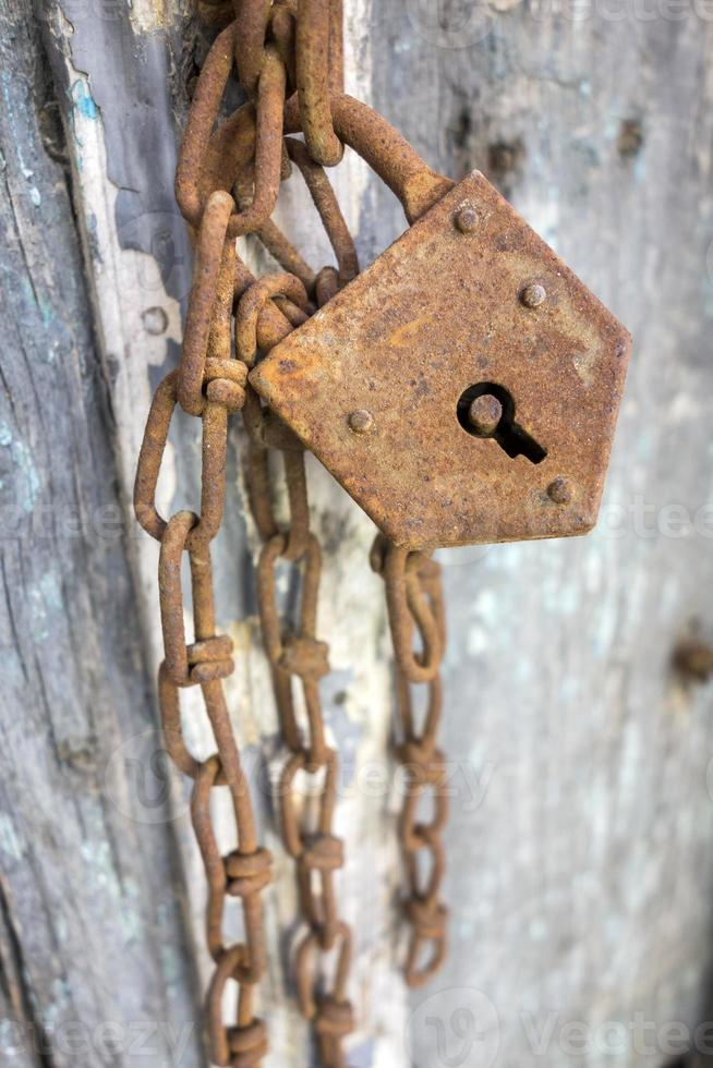 Rusty lock on a wooden door photo
