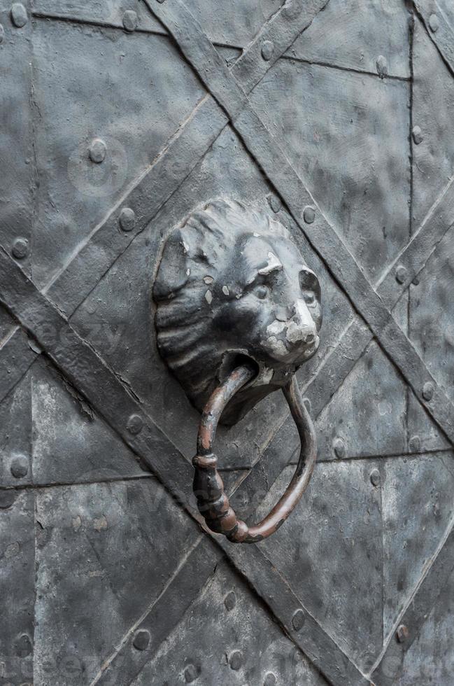 Antigua puerta de hierro con aldaba de cabeza de león foto