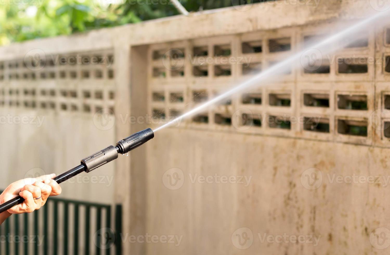 Mujer limpieza waill con chorro de agua a alta presión foto