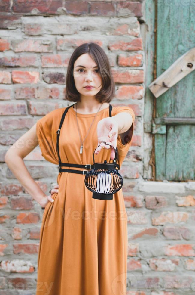 Beautiful black-haired girl posing with a lantern photo