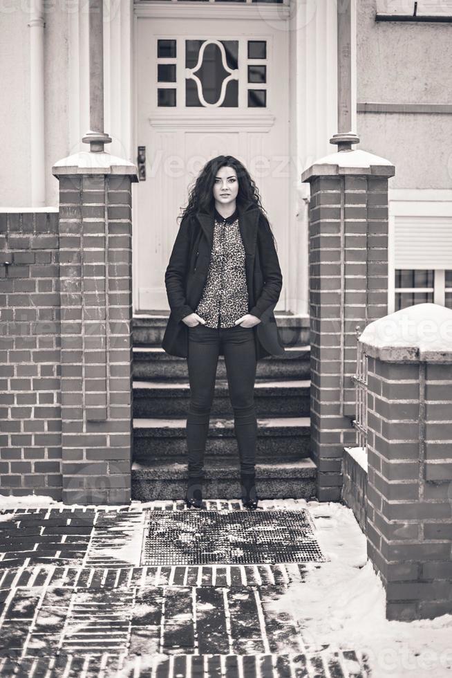 mujer cerca de la puerta de entrada blanca en la calle retro foto