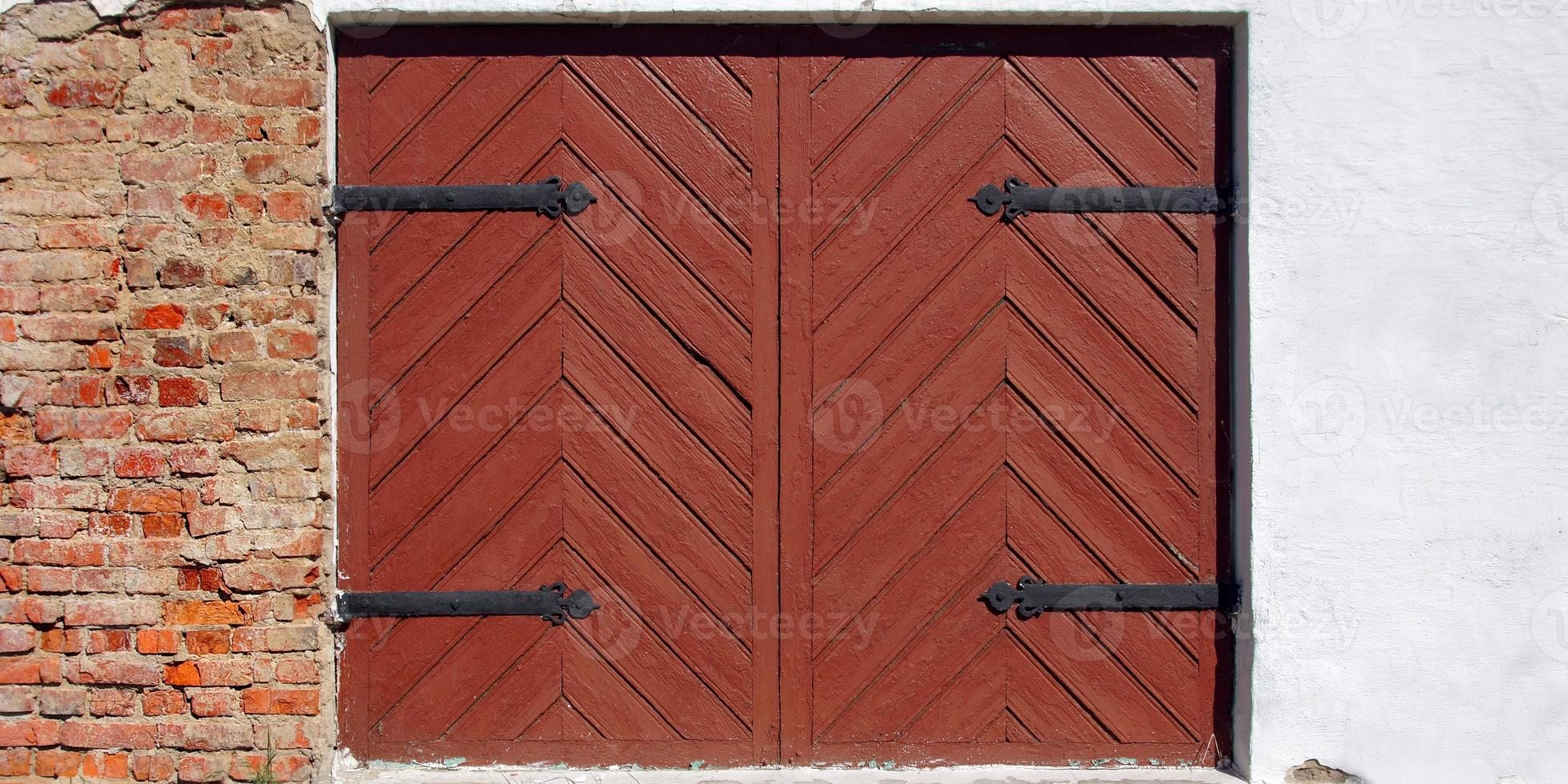 Ancient wooden gate in old building facade. photo