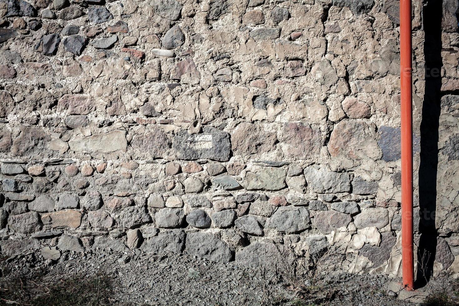 antiguo muro de piedra y tubería foto
