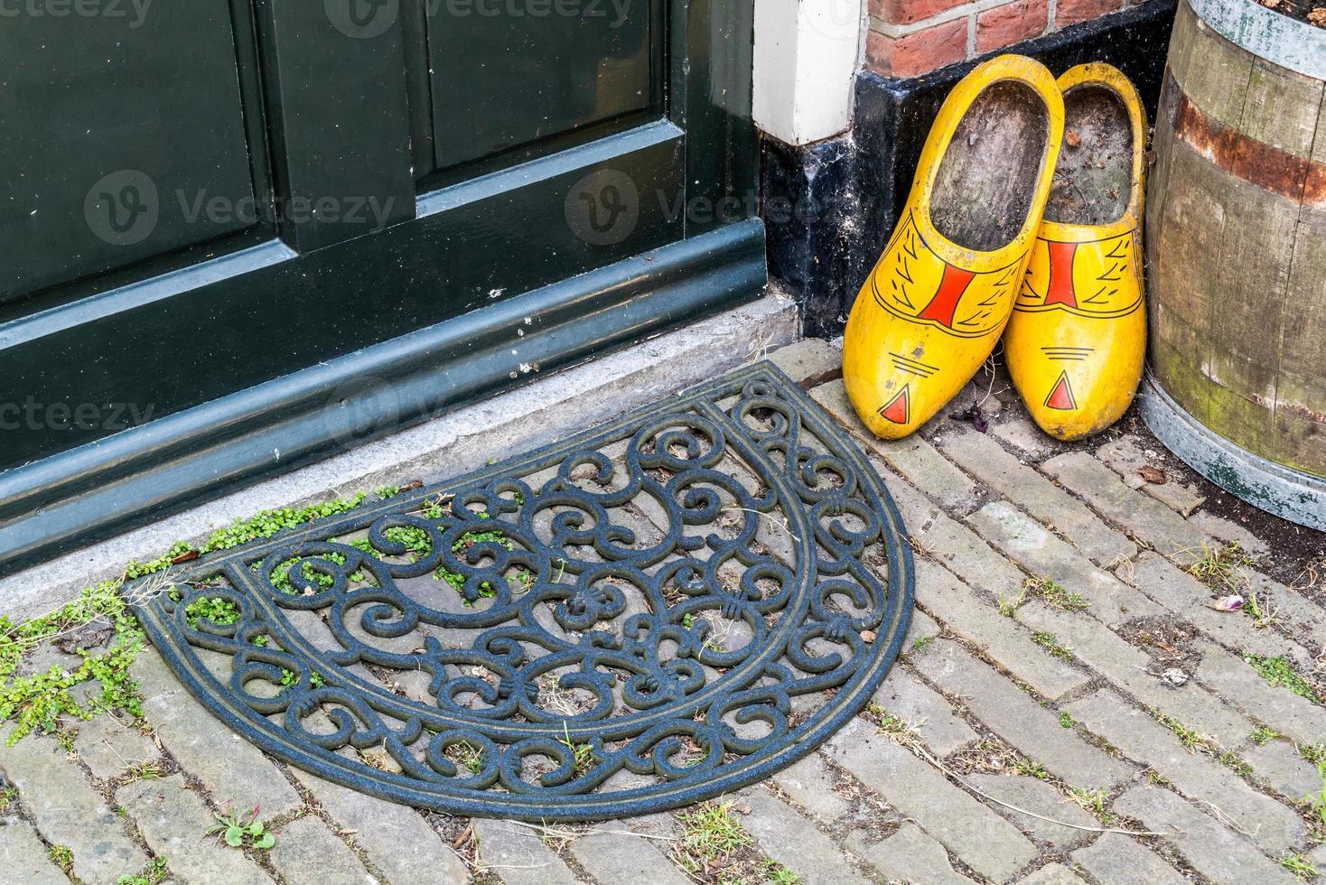 Zapatos de madera y felpudo en la puerta de la antigua casa holandesa foto