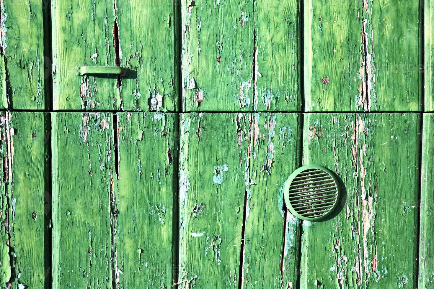 Martinete verde en una puerta de madera cerrada Lonate Ceppino Italia foto
