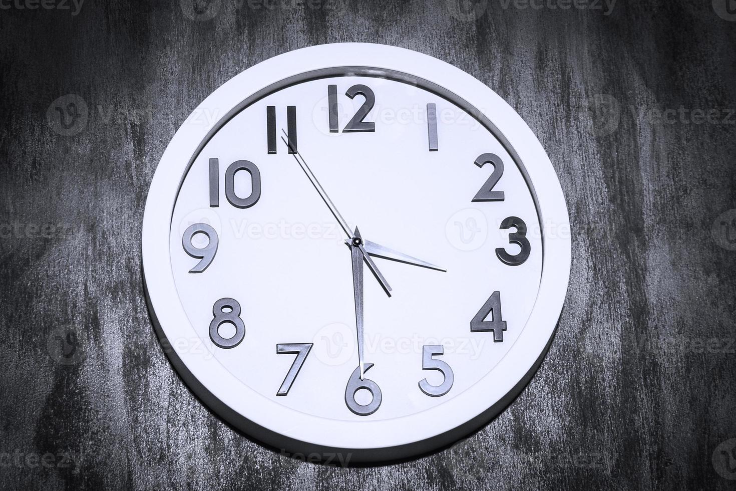 Reloj moderno en un sucio muro de hormigón foto
