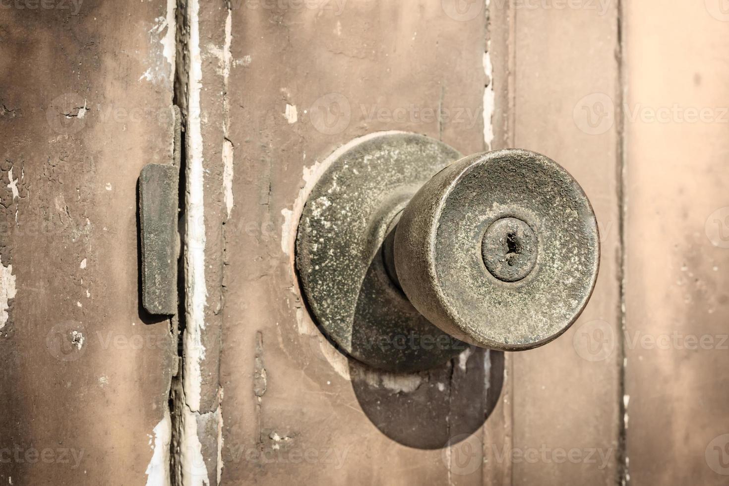 Pomo de puerta rústica en la antigua puerta de madera. foto