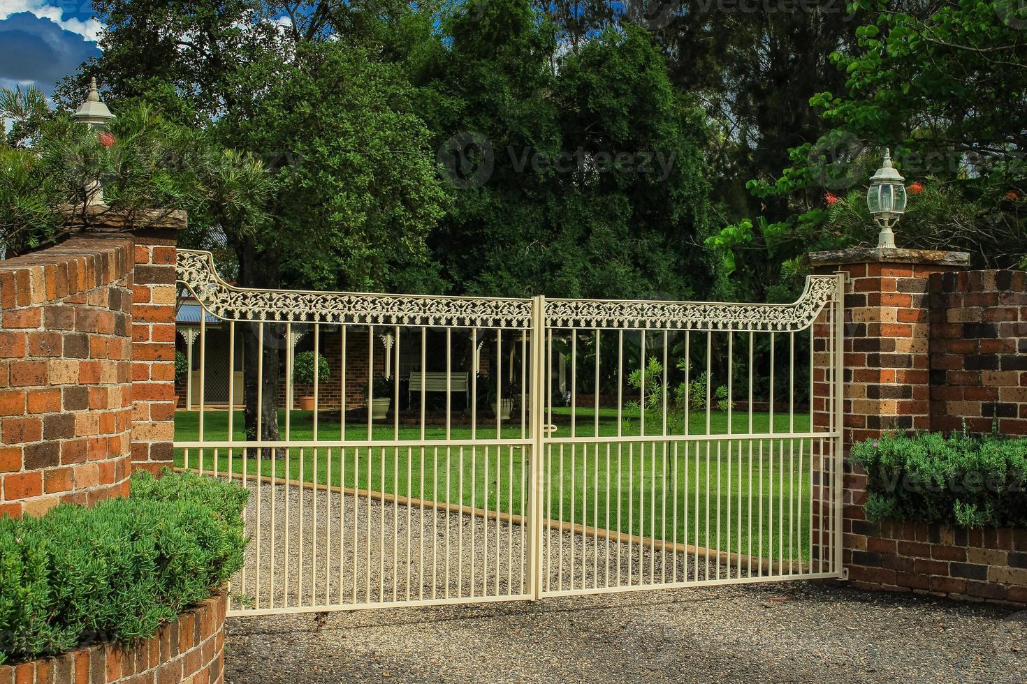 Puertas de entrada de entrada de metal en valla de ladrillo foto