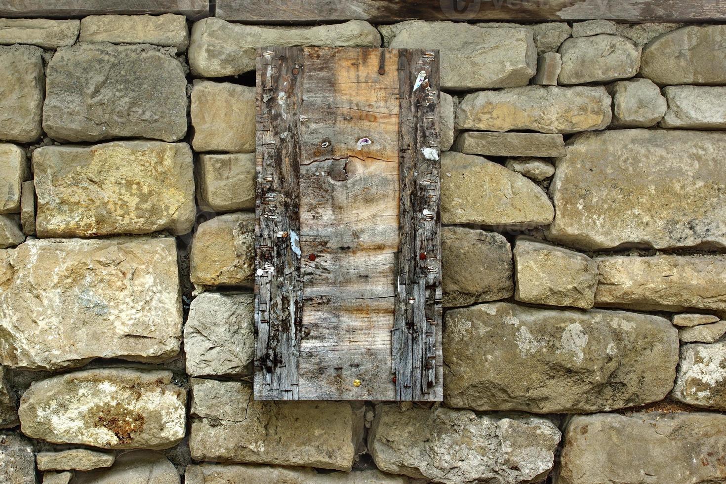 Letrero de madera vintage en el antiguo muro de piedra foto