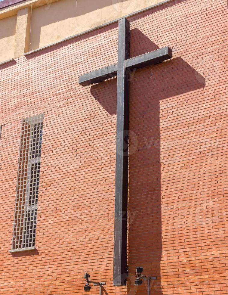 large iron cross on the facade of a Catholic church photo