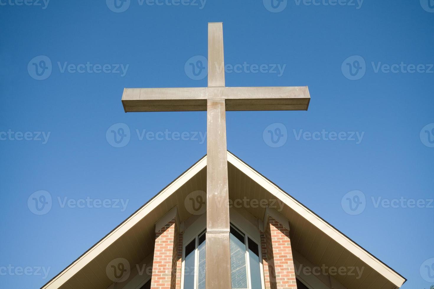 Cruz delante del techo de la iglesia cielo azul foto