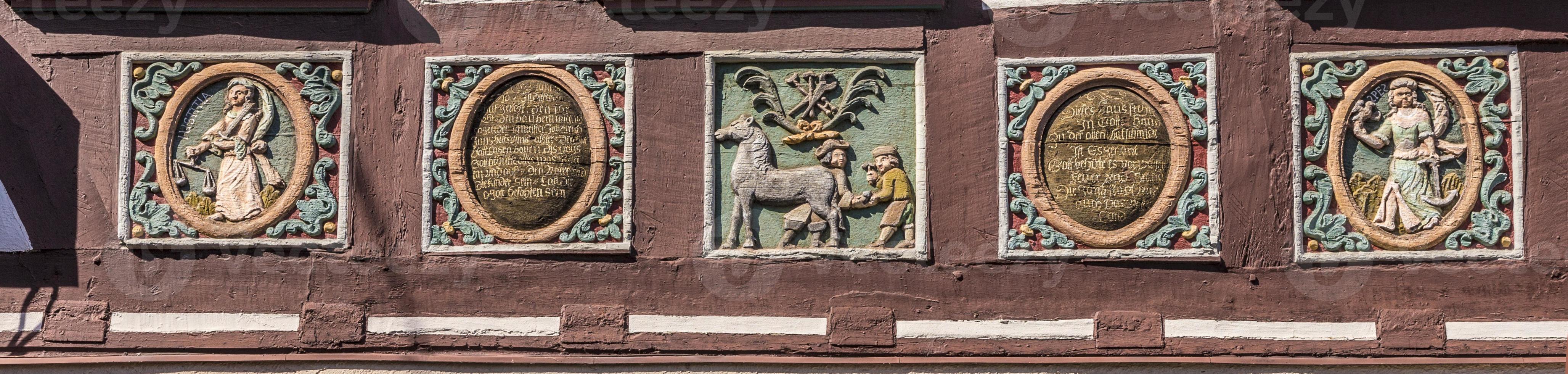 Talla tradicional en una casa de entramado de madera con símbolos foto