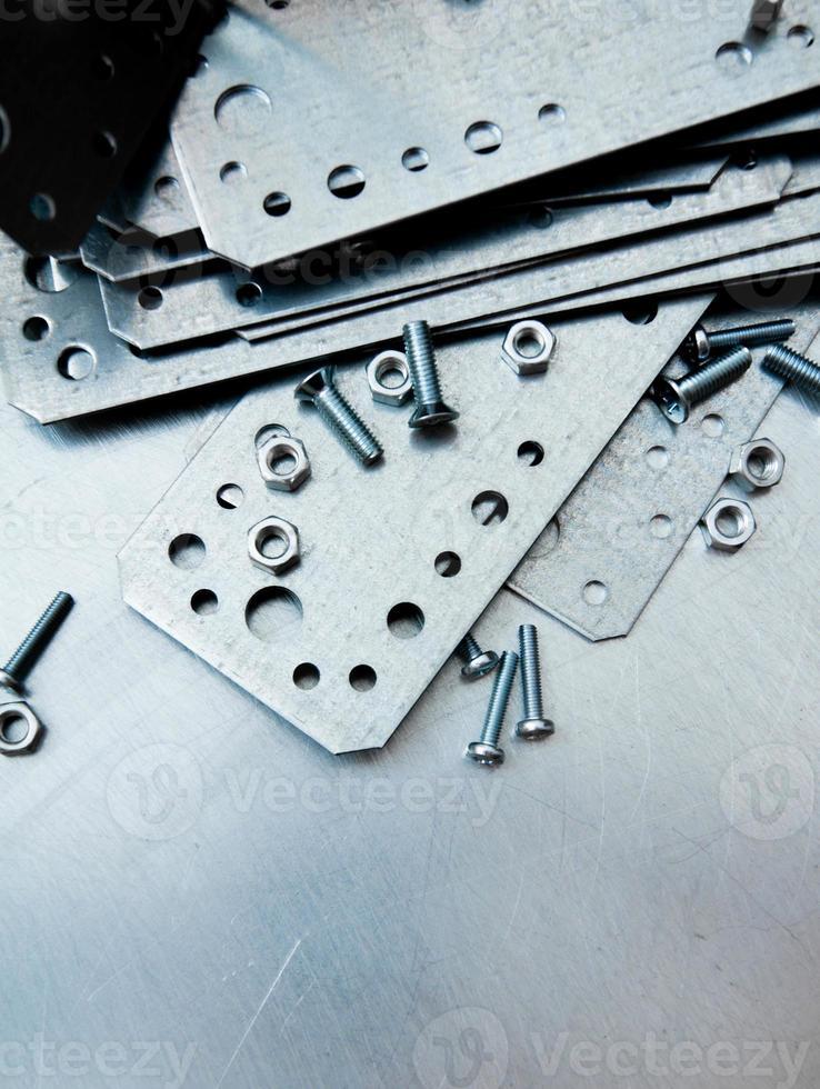 Preparaciones de metal y elementos de fijación en el fondo de metal rayado. foto