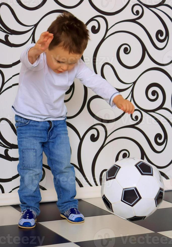 niño pateando pelota foto