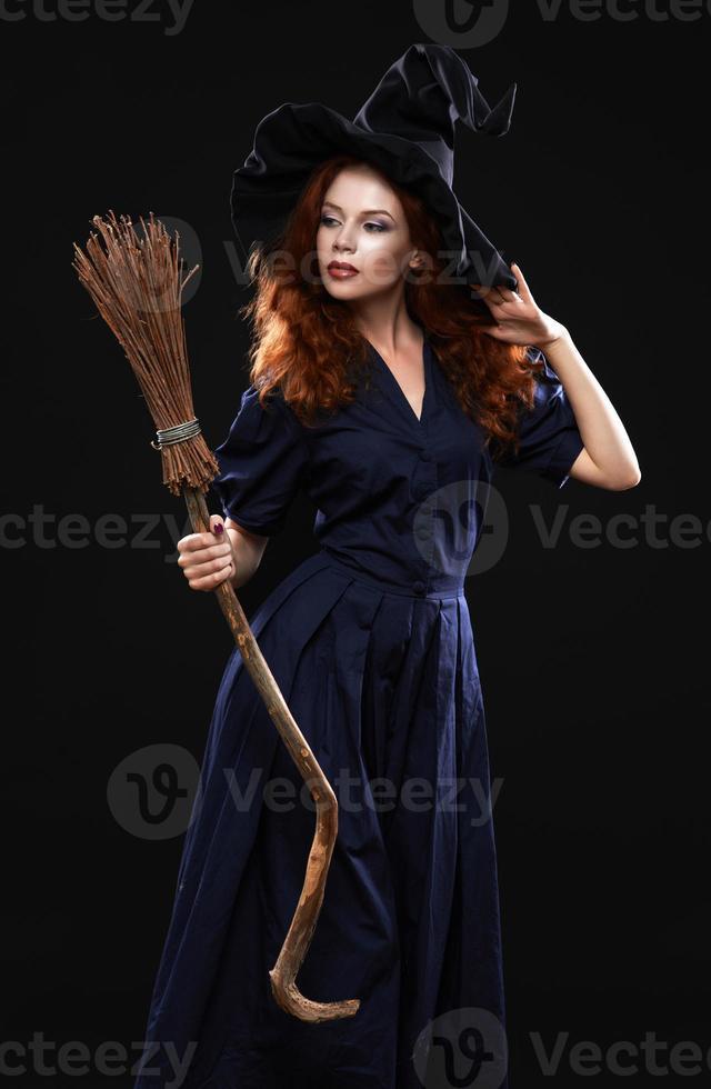 joven hermosa bruja pelirroja en la oscuridad foto