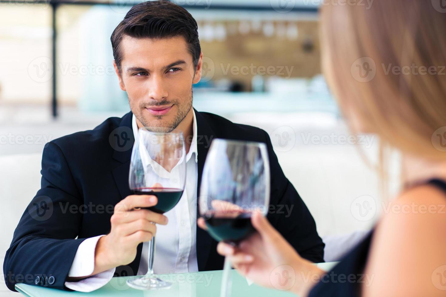 Man drinking red wine with his girlfriend photo
