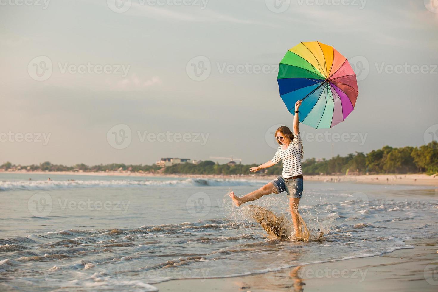 alegre joven con paraguas arco iris divirtiéndose en el foto