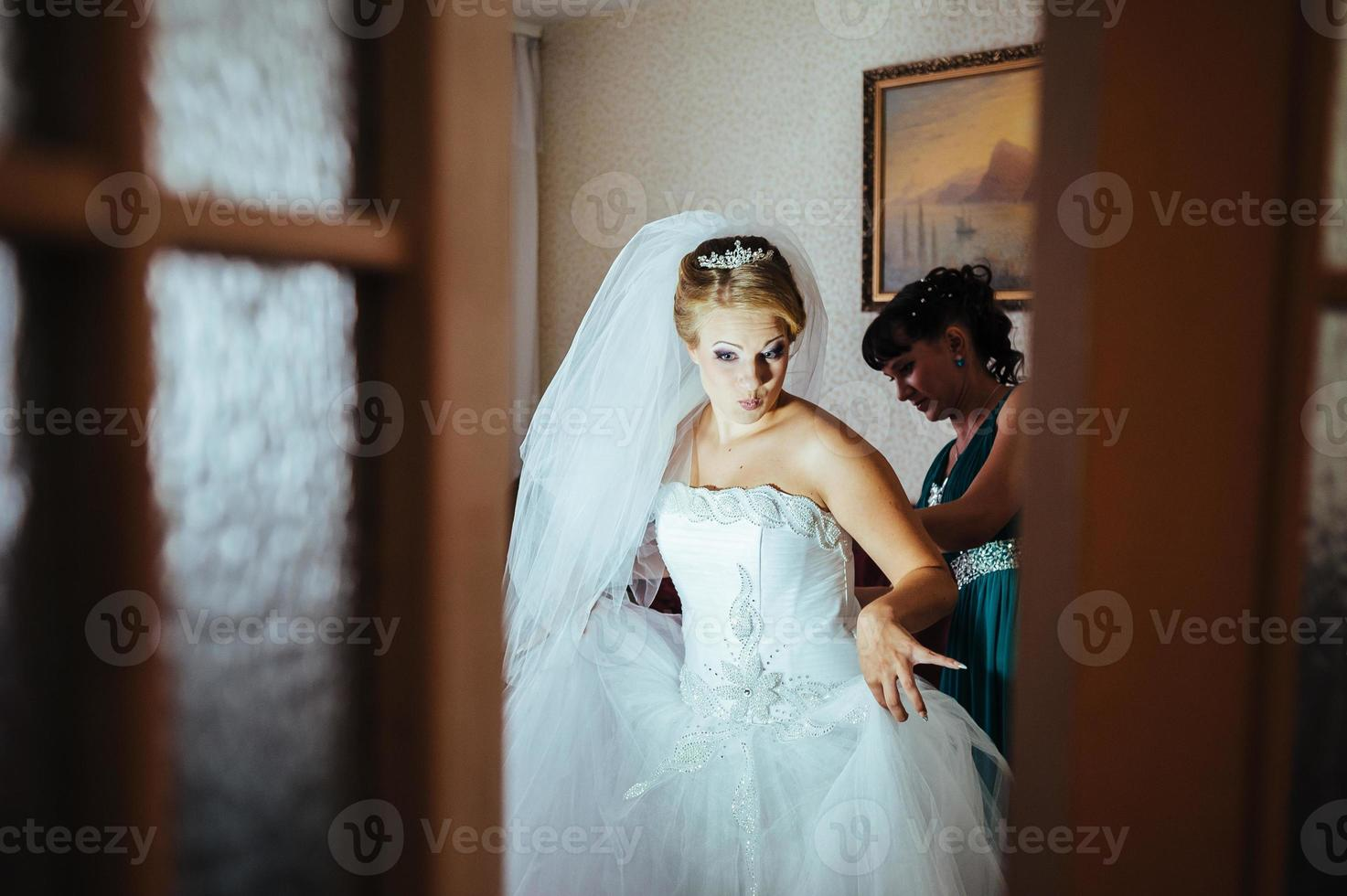 Beautiful caucasian bride getting ready for the wedding ceremony photo