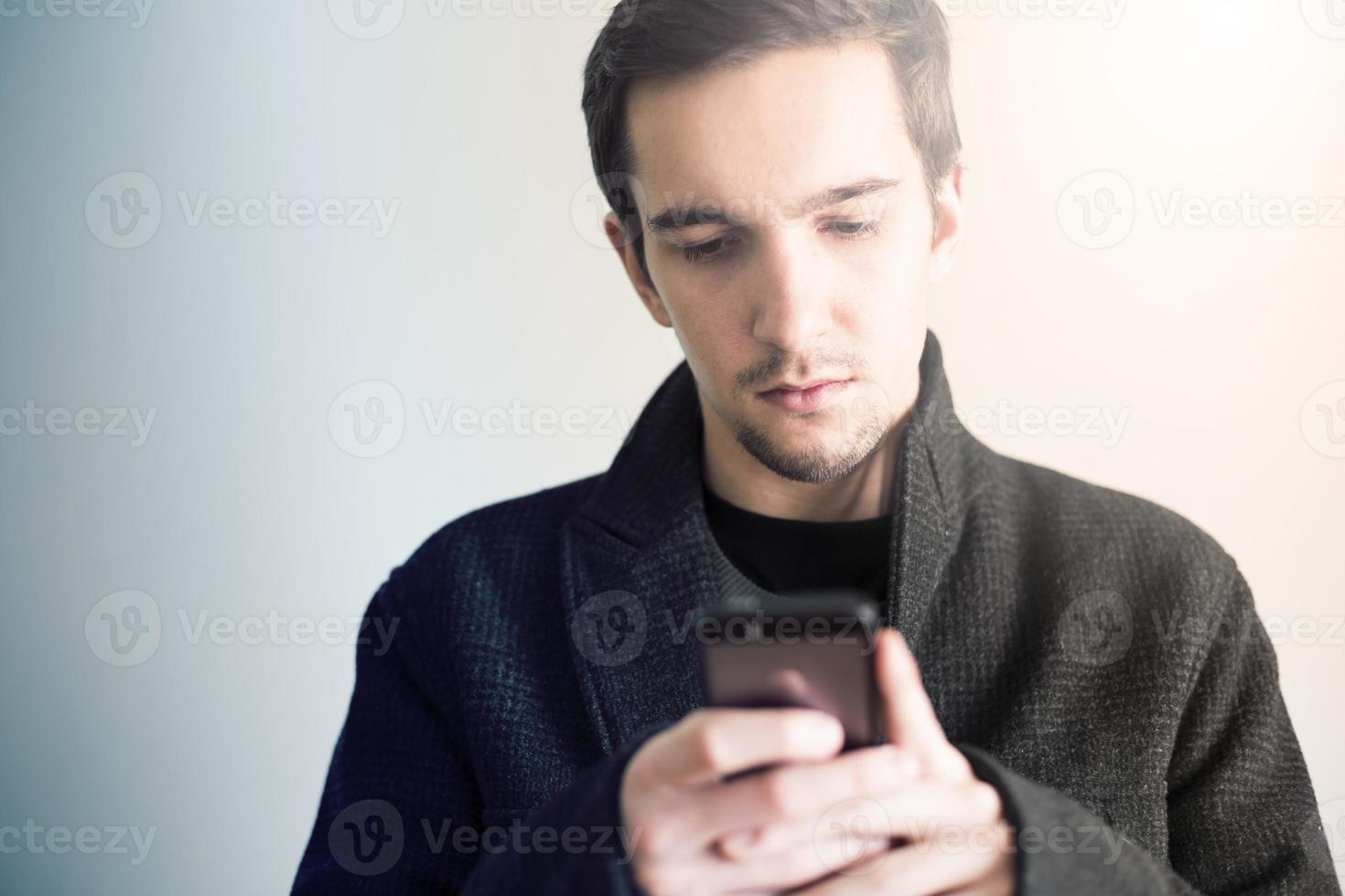 hombre elegantemente vestido con smartphone. foto