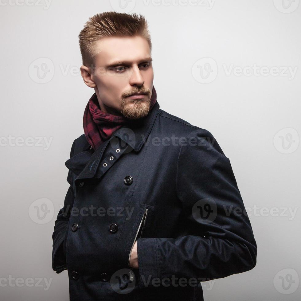Elegant young handsome man in black coat. Studio fashion portrait. photo