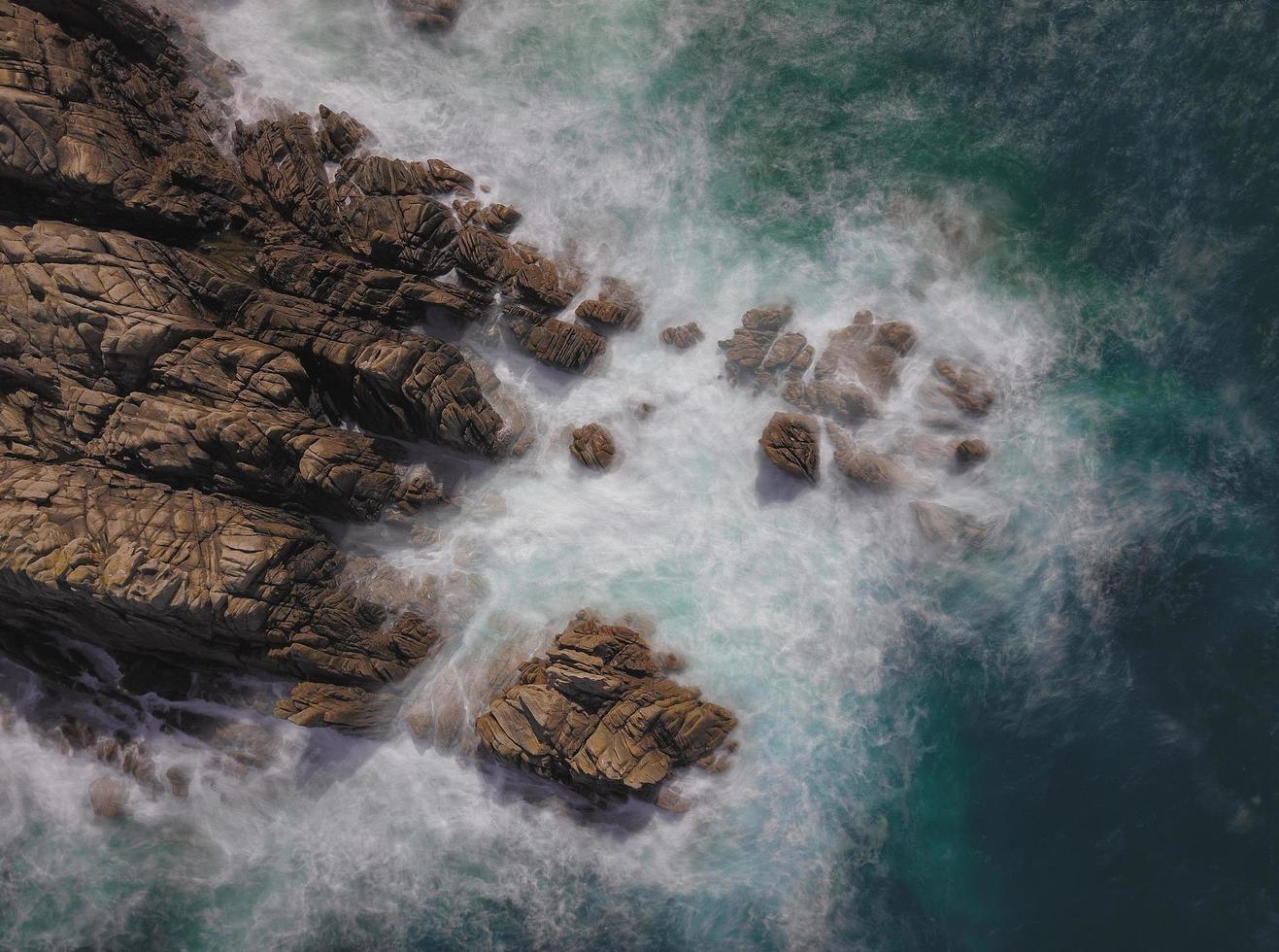 larga exposición de olas salpicando rocas foto