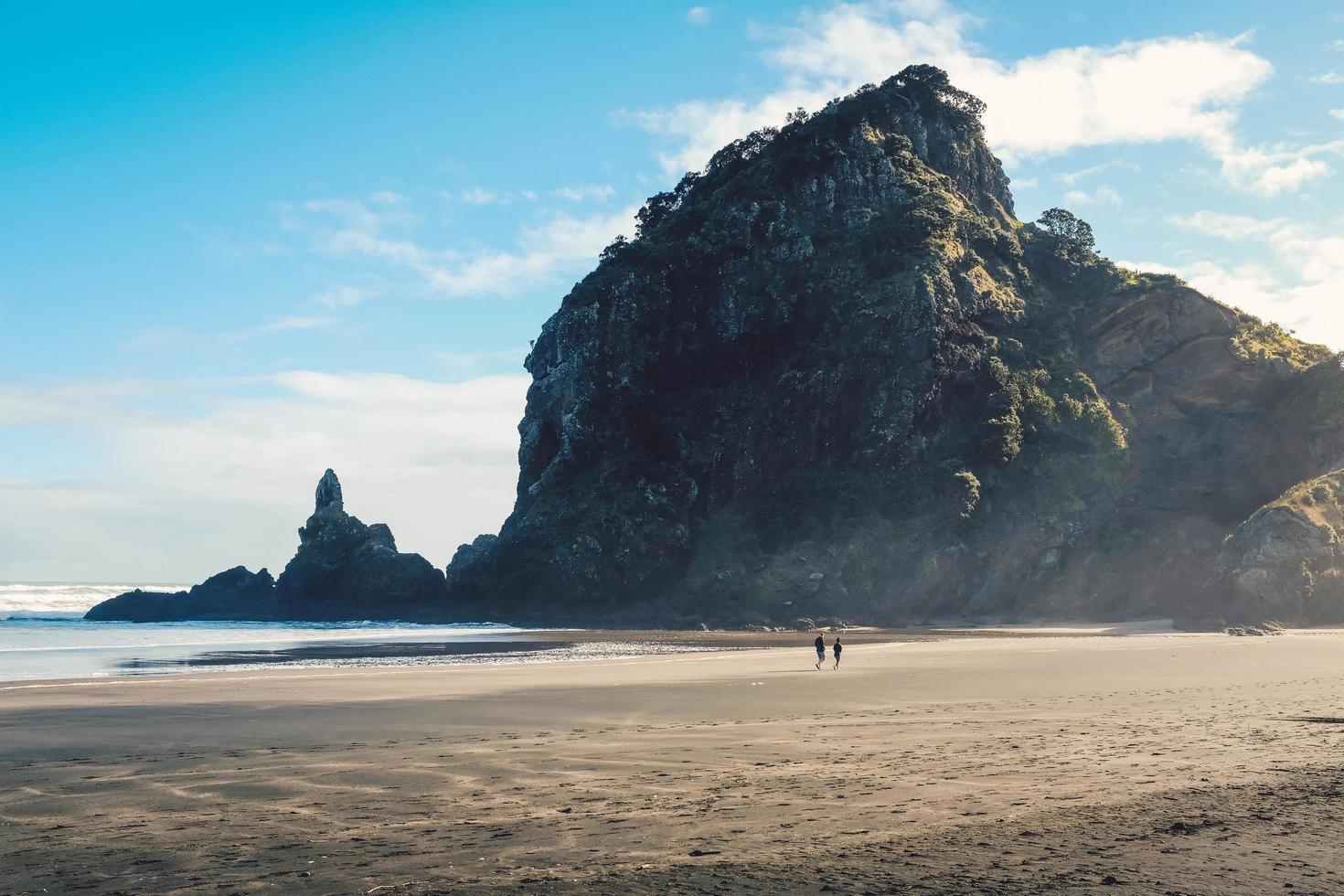 Two people on seashore near mountain photo
