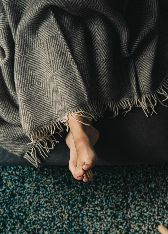 View of person's feet under blanket photo