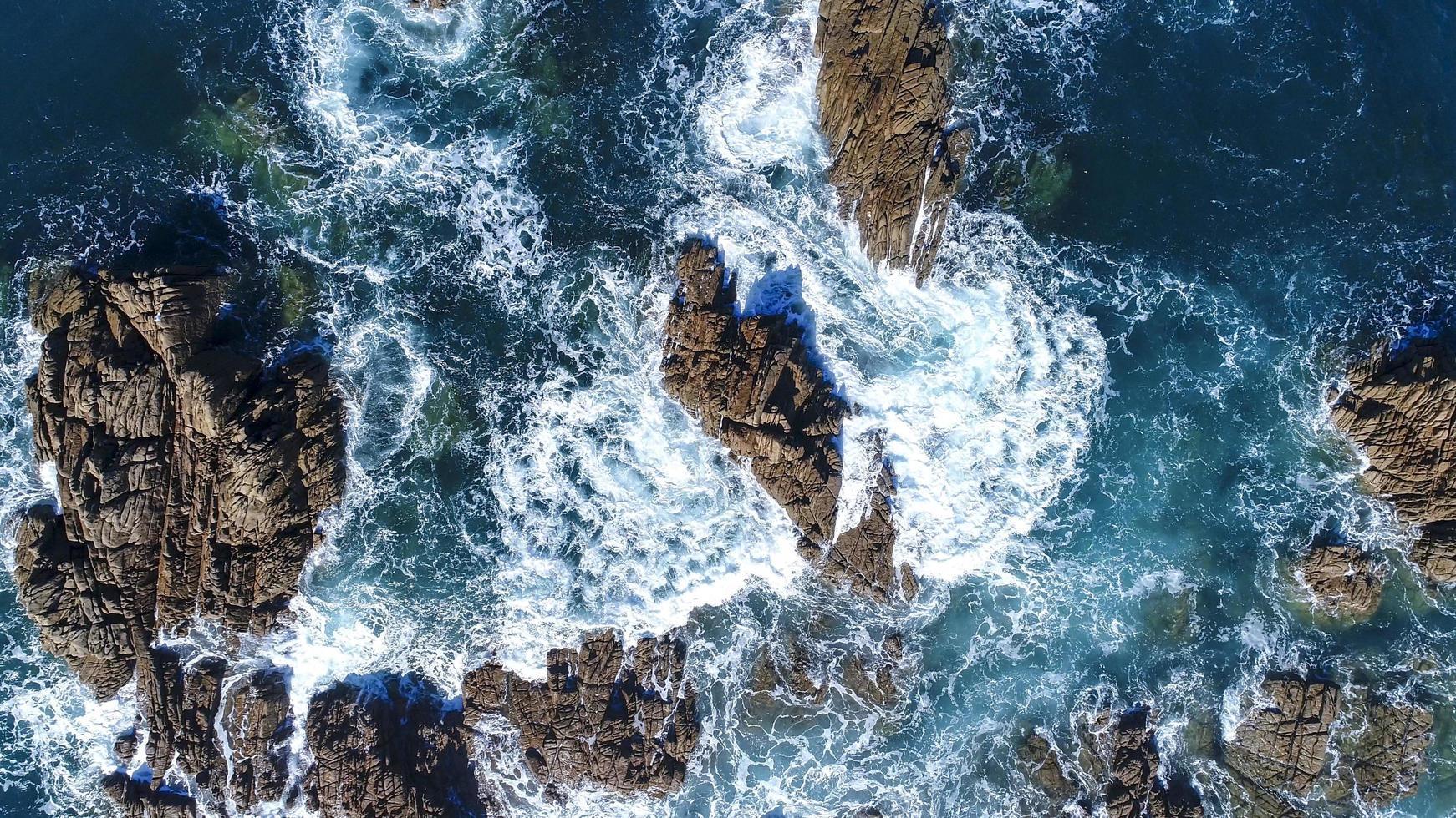 Ocean waves crashing into rocks photo