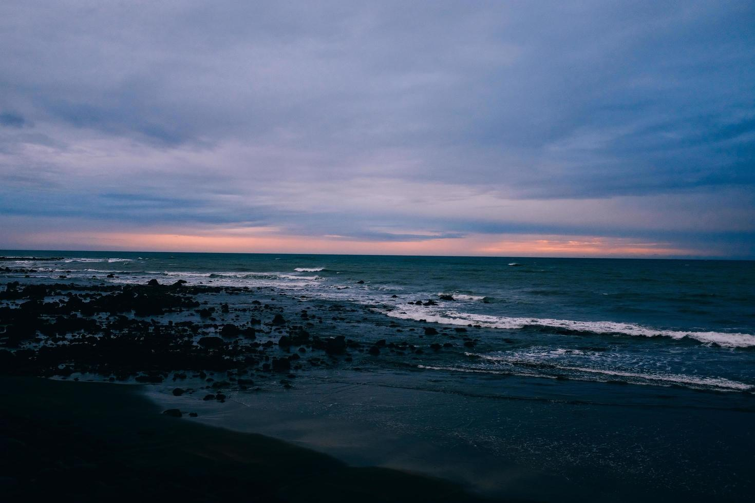 Silhouetted rocks on beach at sunset photo