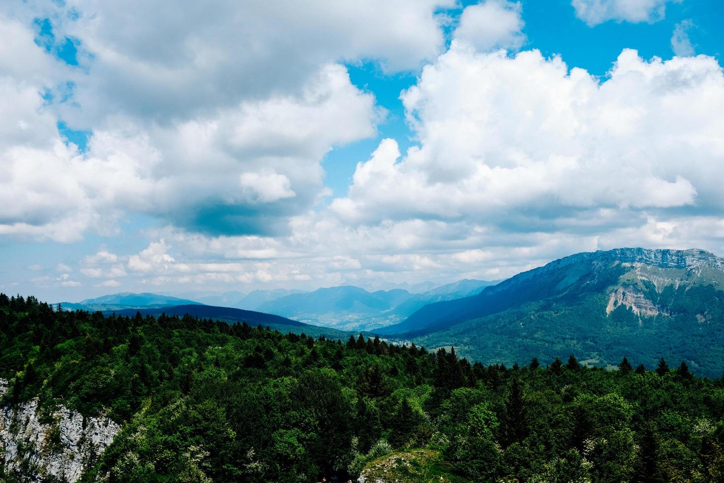 Trees and mountains under cloudy blue sky photo