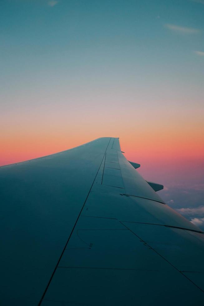 Airplane wing against colorful clear sky photo