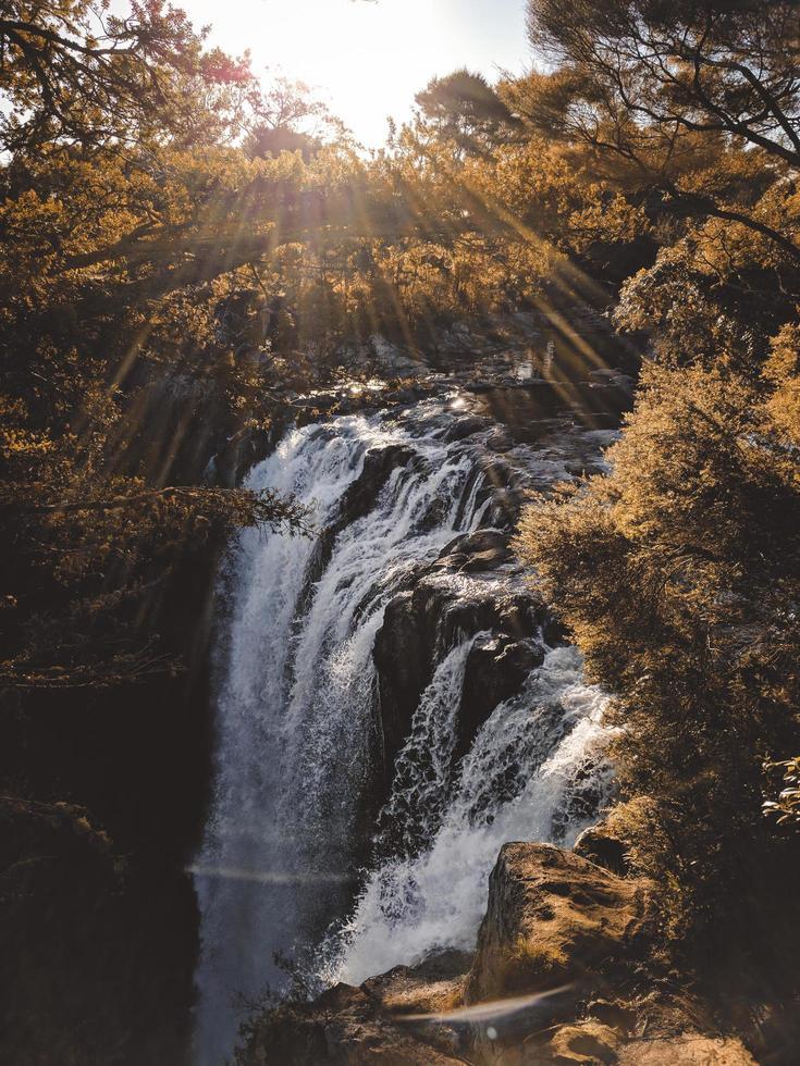 Waterfall among rocks and trees photo
