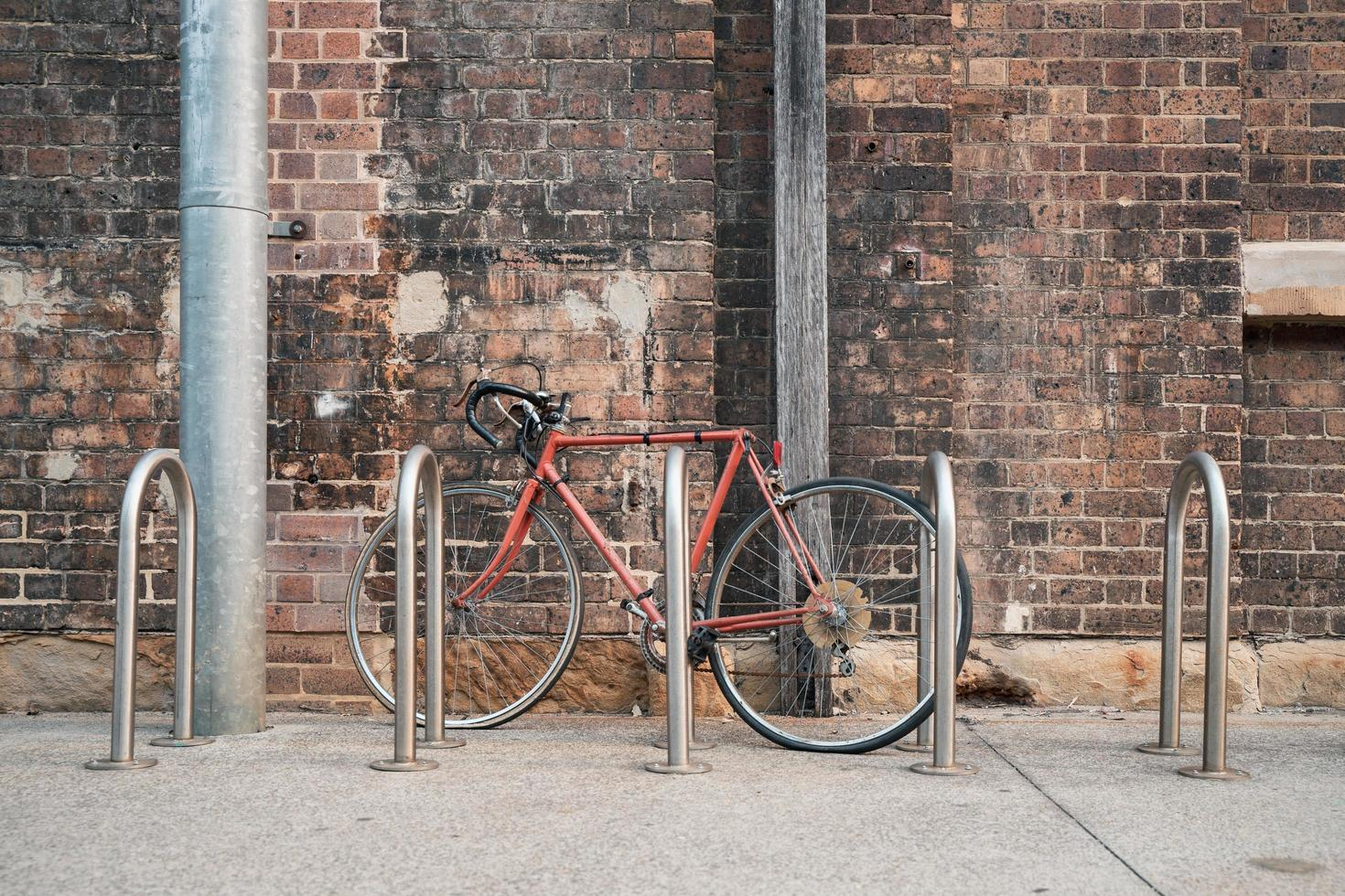Red bike next to bike rack near wall photo
