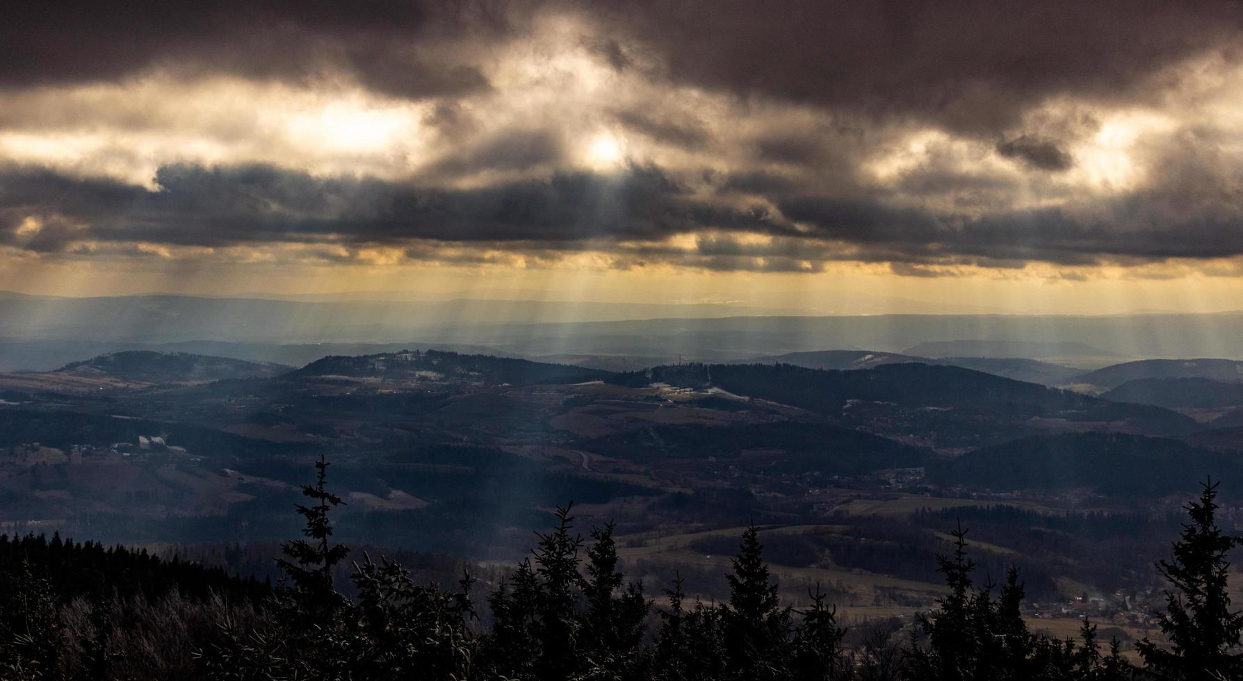 Sunbeams shining through clouds on mountains photo