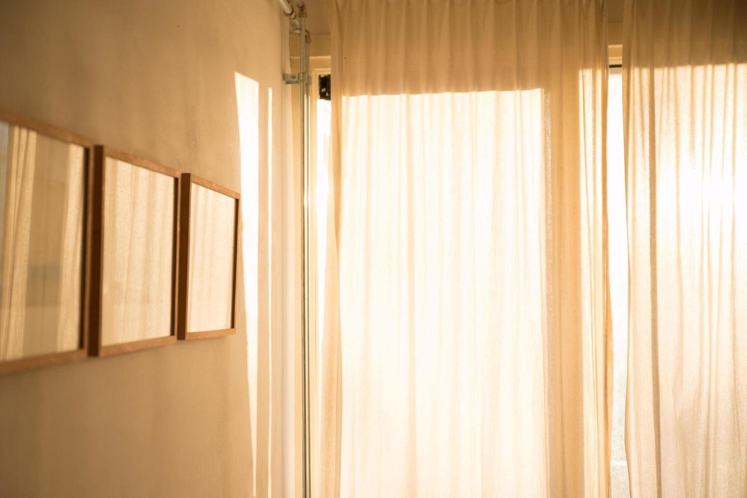 Room with picture frames and window curtains photo