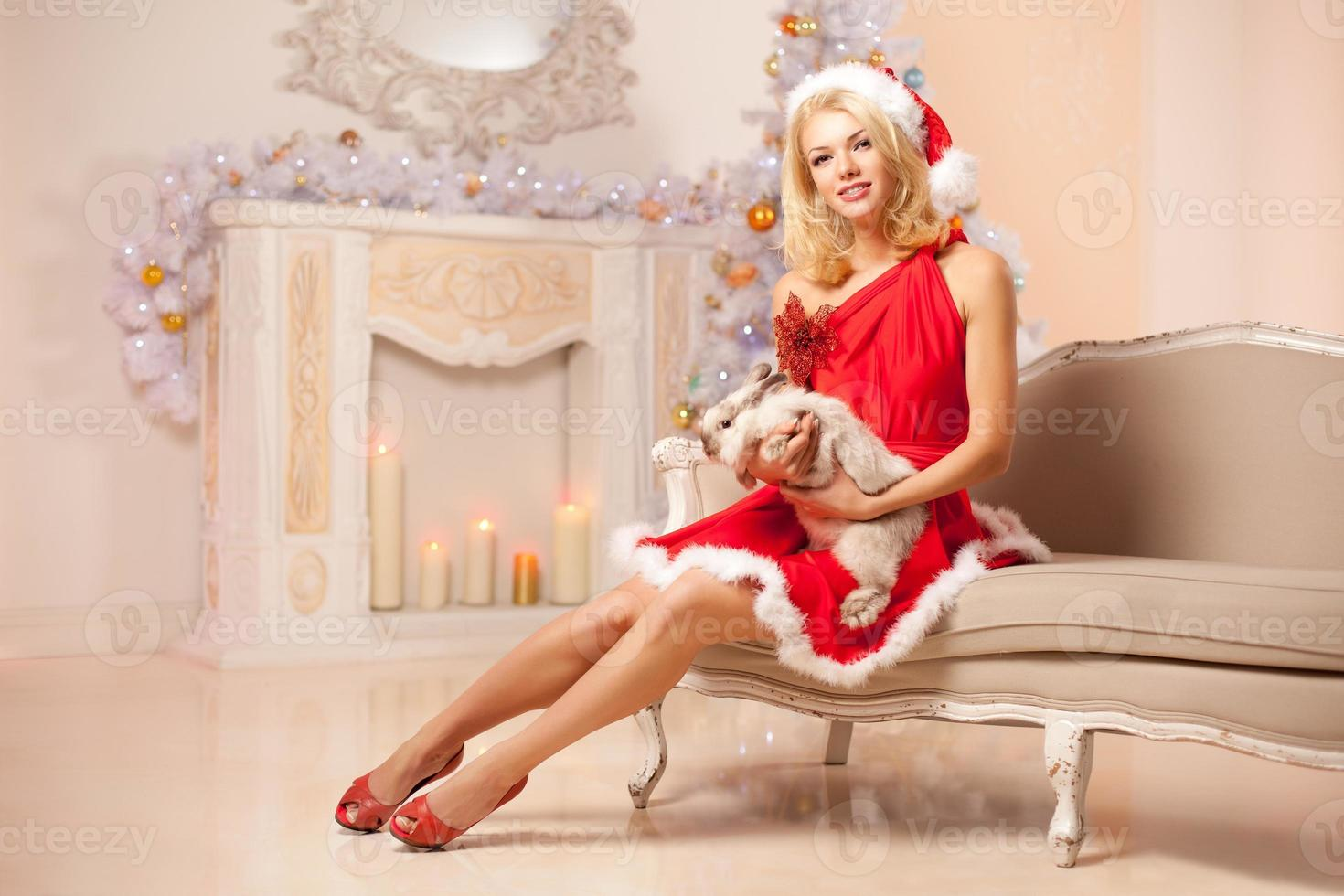 Young beautiful smiling santa woman near the Christmas tree with photo