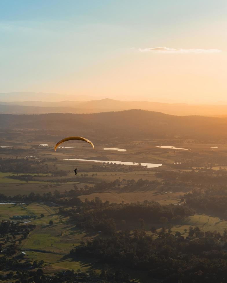 Person paragliding above countryside  photo