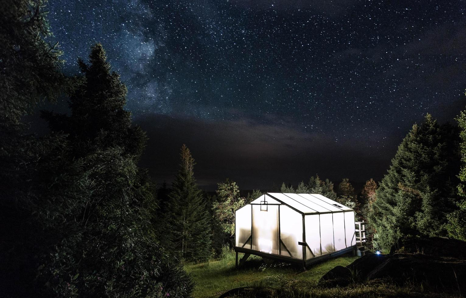 Illuminated camp shelter under starry sky photo