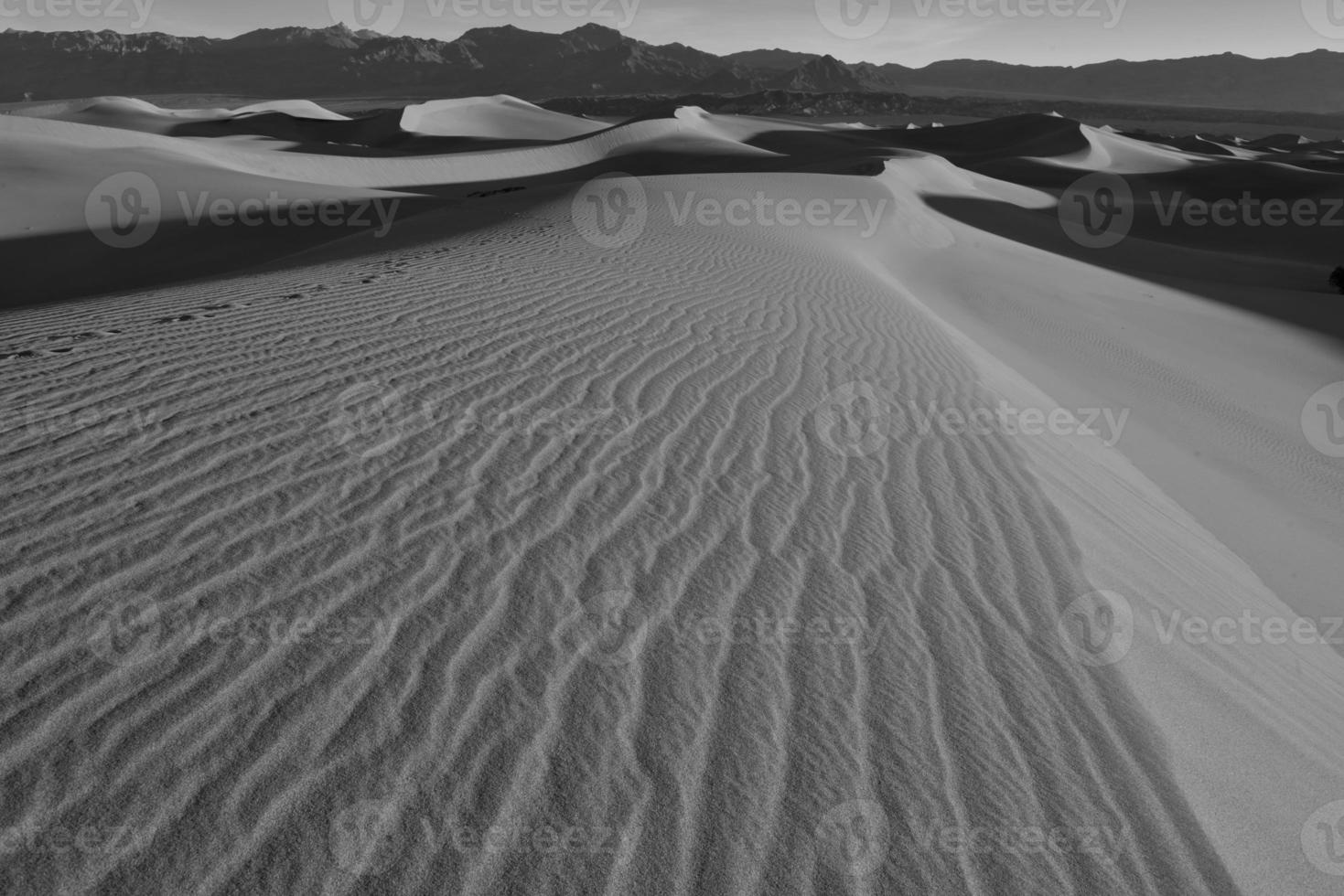 Sand dunes and mountains in desert landscape photo