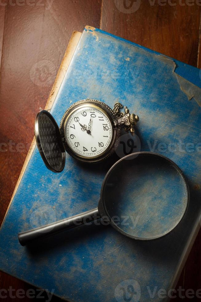 Magnifier and pocket watch on antique book. photo