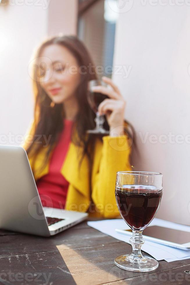 Woman with red wine tablet and laptop in street cafe photo