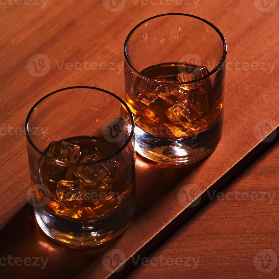 Highball whiskey glass with ice on wooden background. photo