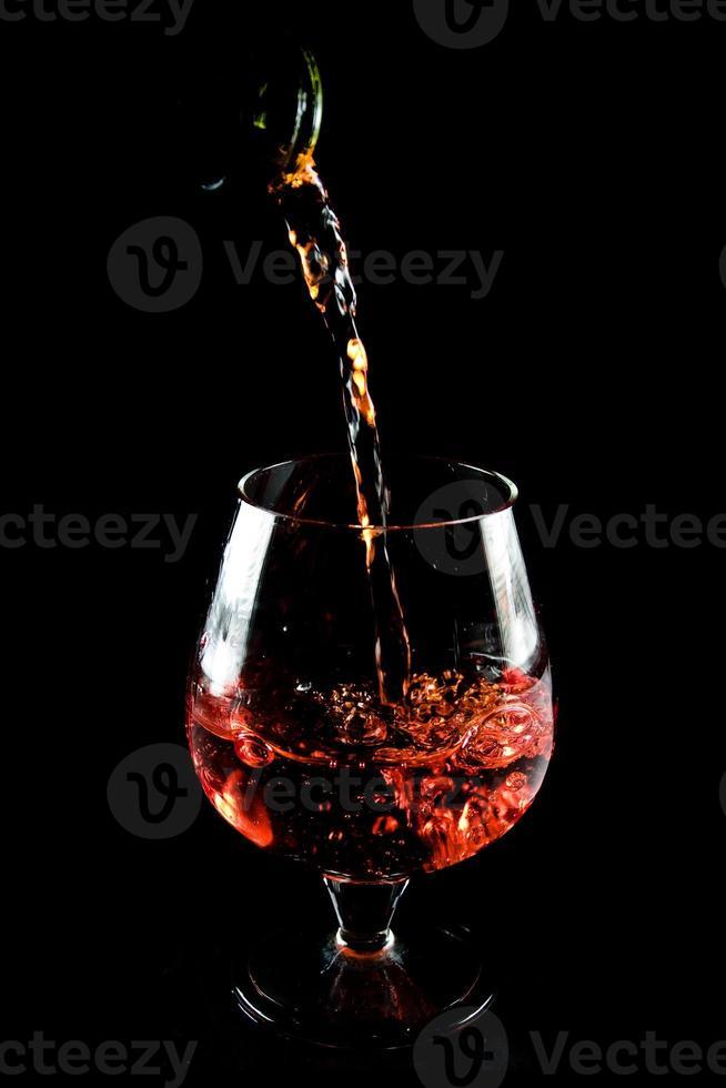 copo de conhaque em um fundo preto foto