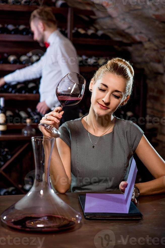 Woman tasting wine in the cellar photo