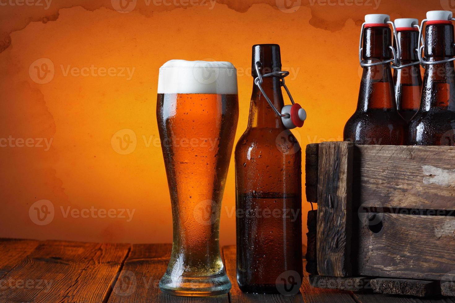 Beer glass with wooden crate with bottles photo