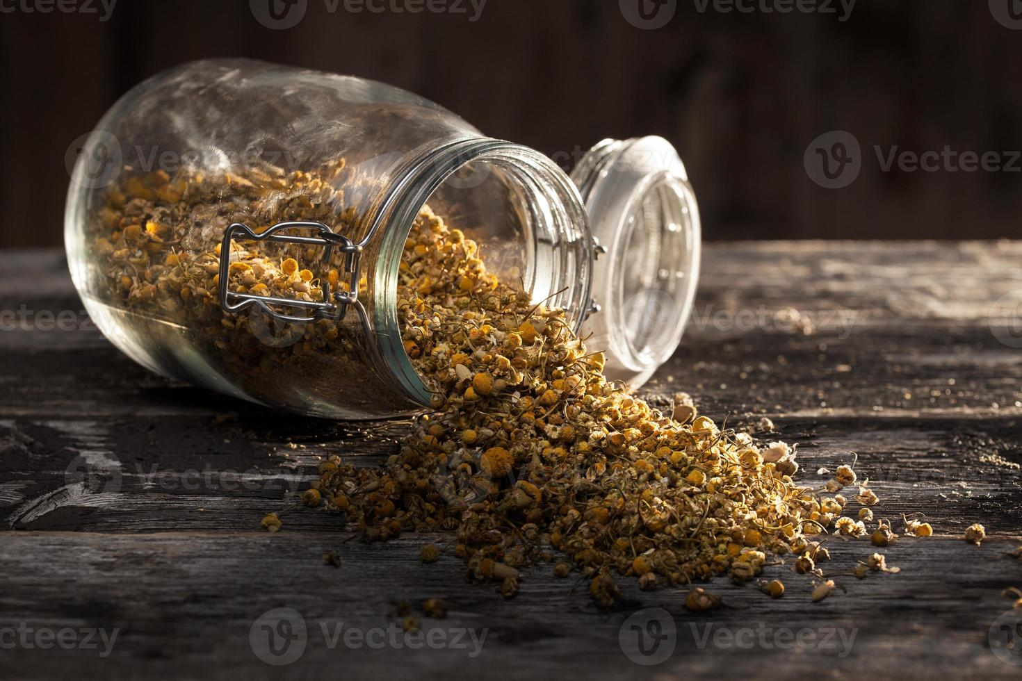 Jar of chamomile flowers open and spilled on table photo