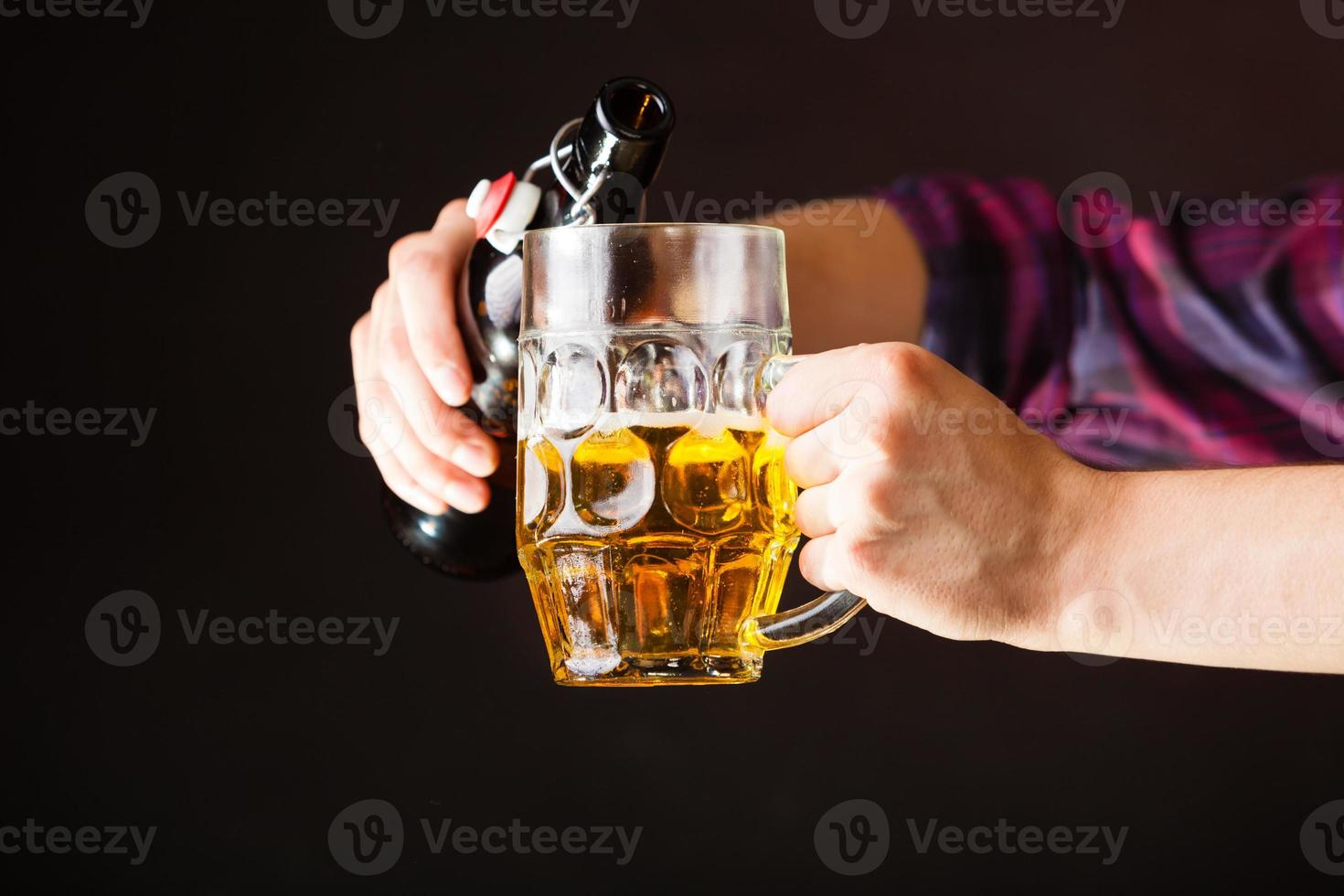 young man pouring beer from bottle into mug photo